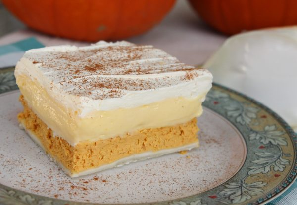 A big square piece of Triple Layer Pumpkin Pie Dessert sprinkled with cinnamon