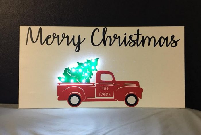 Painted sign Merry Christmas with old red truck and a lighted tree